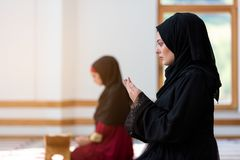 Two Muslim women praying. Inside beutiful mosque Royalty Free Stock Photos