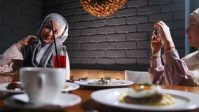 Two muslim women sitting at a table in a restaurant. A woman taking a photo of her friend. Mid shot stock video