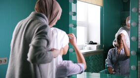 Two muslim women to tie Islamic turban, preparing for a wedding near mirror. Preparing for a wedding stock video footage