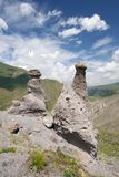 Two natural weathered rocks, blue sky with clouds Stock Images