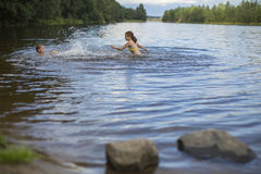Two naughty girls bathe in the lake. Fun. Stock Images