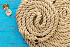 Two neatly coiled ropes and a magnetic compass Royalty Free Stock Photography