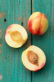 Two nectarines, whole and split on vintage turquoise table Stock Photo