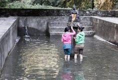 Two nepalese girls buddhist ceremony pray inside holy waterpool. Stock Photos