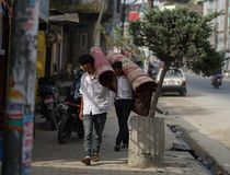 Two Nepali Men Carry on Shoulder Carpet Rug at Thamel Street. Editorial Royalty Free Stock Images