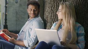 Two nerds flirting with each other sitting on campus park and doing homework. Stock footage stock video footage