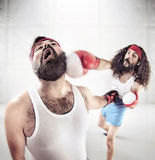 Two nerdy guys boxing on the ring Royalty Free Stock Photography