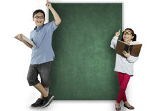 Two nerdy students thinking an inspiration. Two nerdy students holding a book while thinking an inspiration and standing near the blank chalkboard Royalty Free Stock Images