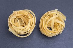 Two nests of traditional Italian pasta. Typical Italian pasta with spaghetti or yellow noodles in the shape of a nest stock photo