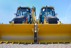 Two new bulldozers on a showcase.  Royalty Free Stock Photography
