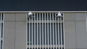 Two new cameras are hanging on a modern building. metal tile lattice design. background technology security camera. Monitoring people controll private lives stock footage