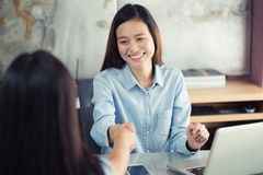 Two new generation business women shaking hands. Two new generation business woman shaking hands,Asian business woman shaking hands with a smile,concept close a Royalty Free Stock Photography