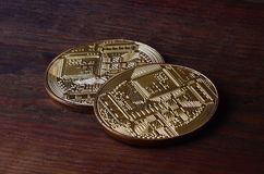 Two new golden physical bitcoins lies on dark wooden backgound, close up. High resolution photo. Cryptocurrency mining concep. T stock photography
