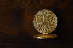 Two new golden physical bitcoins lies on dark wooden backgound, close up. High resolution photo. Cryptocurrency mining concep. T Stock Image
