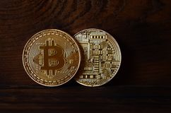 Two new golden physical bitcoins lies on dark wooden backgound, close up. High resolution photo. Cryptocurrency mining concep. T Stock Images