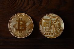 Two new golden physical bitcoins lies on dark wooden backgound, close up. High resolution photo. Cryptocurrency mining concep. T Royalty Free Stock Photography