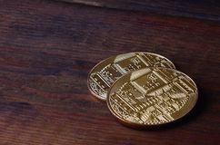 Two new golden physical bitcoins lies on dark wooden backgound, close up. High resolution photo. Cryptocurrency mining concep. T Royalty Free Stock Photos