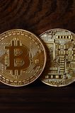 Two new golden physical bitcoins lies on dark wooden backgound, close up. High resolution photo. Cryptocurrency mining concep. T Stock Photo