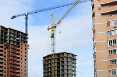 Two new homes. Two buildings under construction and two construction cranes Stock Photo