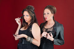 Two New Jersey housewives do makeup. Two sexy middle-aged New Jersey style housewives dressed in black prepare their makeup Stock Images