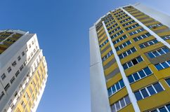 Two new multi-storey houses, painted in yellow and blue on the sky. stock image
