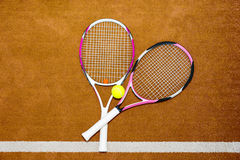 Two new pink tennis rackets with a tennis ball on a clay court o. Utdoors in summer or spring Royalty Free Stock Photos
