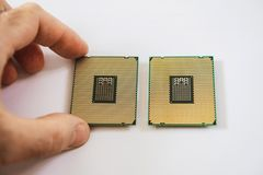 Two new powerful workstation CPU processors man hand. Man hand comparing two new powerful workstation CPU processors before service new computer workstation stock images