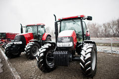 Two new red tractor stay at snowy weather background combaine Stock Photography