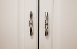 Two New Stylistic Hinges. Closeup view on new stylistic hinges on white closet Royalty Free Stock Photo