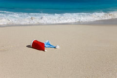 Two New Years caps of Santa Claus on beach.  stock photography