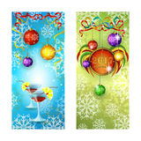 Two New Year`s greeting banner. Two glasses with a festive cocktail. And Christmas balls on a blue background with snowflakes and stars. Decorative composition Royalty Free Stock Photo
