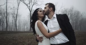 Two newlyweds look at each other and embracing with smile 4k stock footage