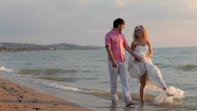 Two Newlyweds Walking Along The Shore. Two lovers walk a newlywed on sea beach stock video