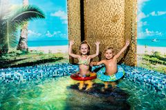 Two nice children swiming in blue pool stock photo