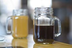 Two coffees in a mason jars. Two nice cups of coffee in a glass mason jar mugs in a coffee shop while studying for college Royalty Free Stock Photos