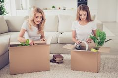 Two nice cute attractive lovely winsome charming blonde cheerful cheery ladies opening boxes with things new life. Mortgage relocation in light white interior royalty free stock images
