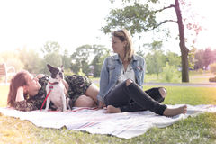 Two friends woman with terrier dog outside at the park. Two nice friends women with terrier dog outside at the park Royalty Free Stock Photography