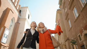 Two Nice Girlfriends are Walking in City in Old Street, Laughing and Hugging stock footage