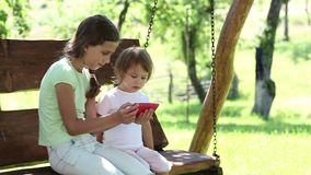 Two nice girls with red smartphone sits on the swing bench in garden. Two sisters with red cell phone sits on the swing bench stock footage