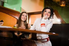 Two nice girls at table Royalty Free Stock Photos