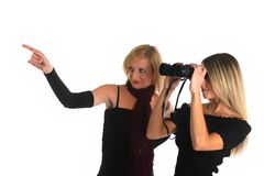 Two nice girls watching something with a binocular Royalty Free Stock Photos