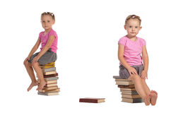 Two nice little girls sitting on stack of books Royalty Free Stock Photography