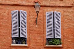 Two nice windows on the brick wall with window sha Royalty Free Stock Images