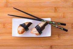 Two nigiri eel sushi with chopstick on bamboo board Stock Photo