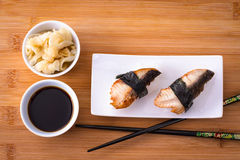 Two nigiri sushi eel with soy sauce on bamboo board Royalty Free Stock Images