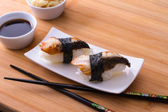 Two nigiri sushi eel with soy sauce on bamboo table Stock Image