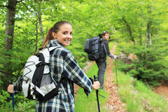 Two nordic walkers. Young couple enjoying nordic walking in a forest Royalty Free Stock Photos