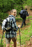 Two nordic walkers. Young couple enjoying nordic walking in a forest, women looking at camera Stock Photo