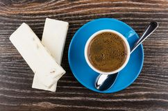 Two nougats, coffee in cup, spoon on saucer on table. Two nougats, coffee in blue cup, spoon on saucer on wooden table. Top view royalty free stock photo