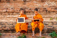 Two novice reading and studying blackboard with funny in old temple at sunset time, Ayutthaya Province stock photography